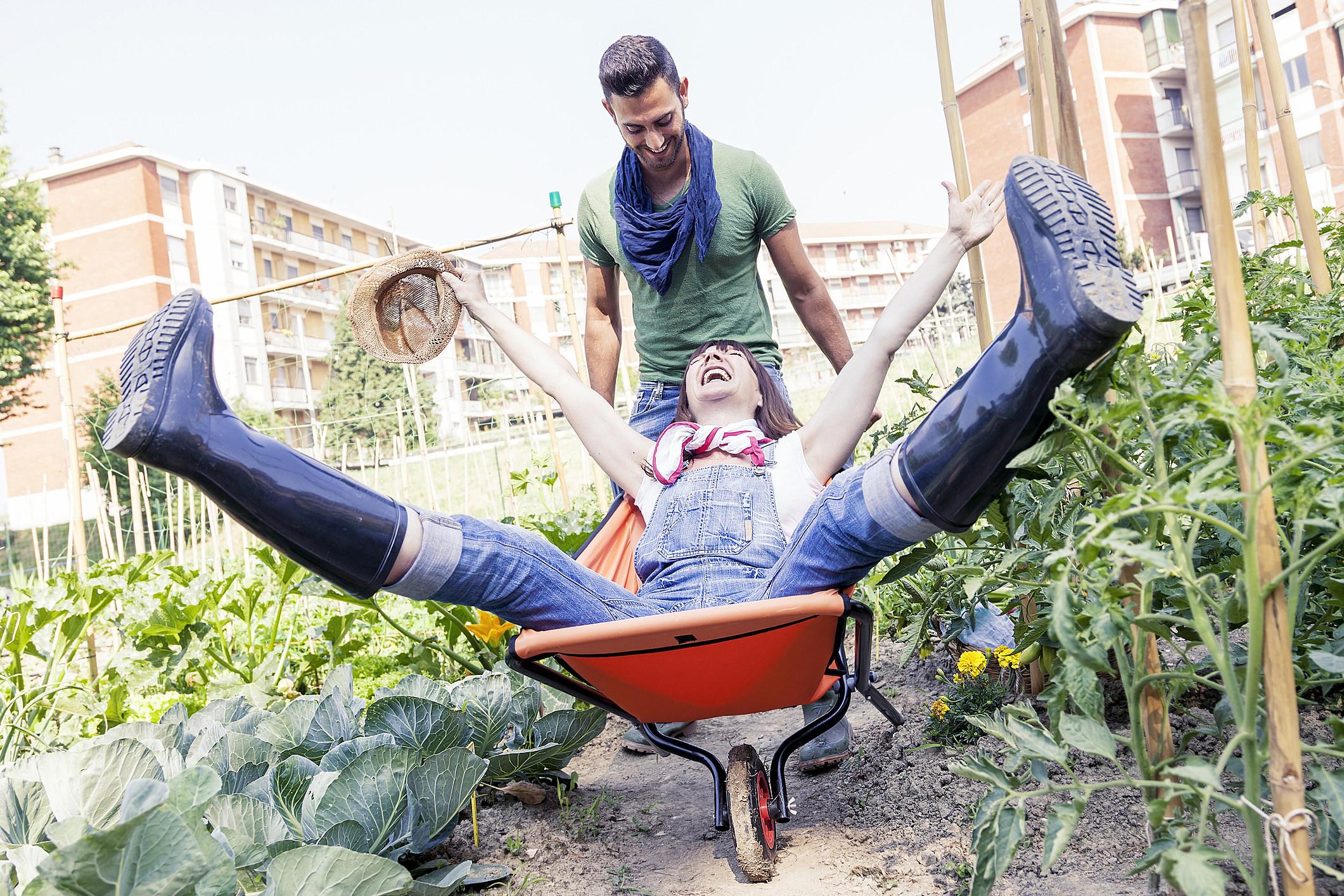 man pushes his girlfriend in wheelbarrow in the garden