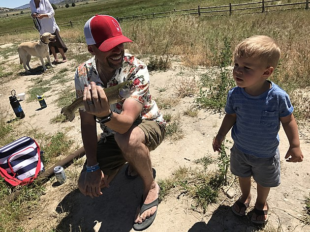 Kekeluv and Lennox staring at his first ever fish caught this Summer.